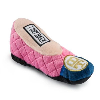 A plush dog toy shaped like a woman's foot in a pink shoe.
